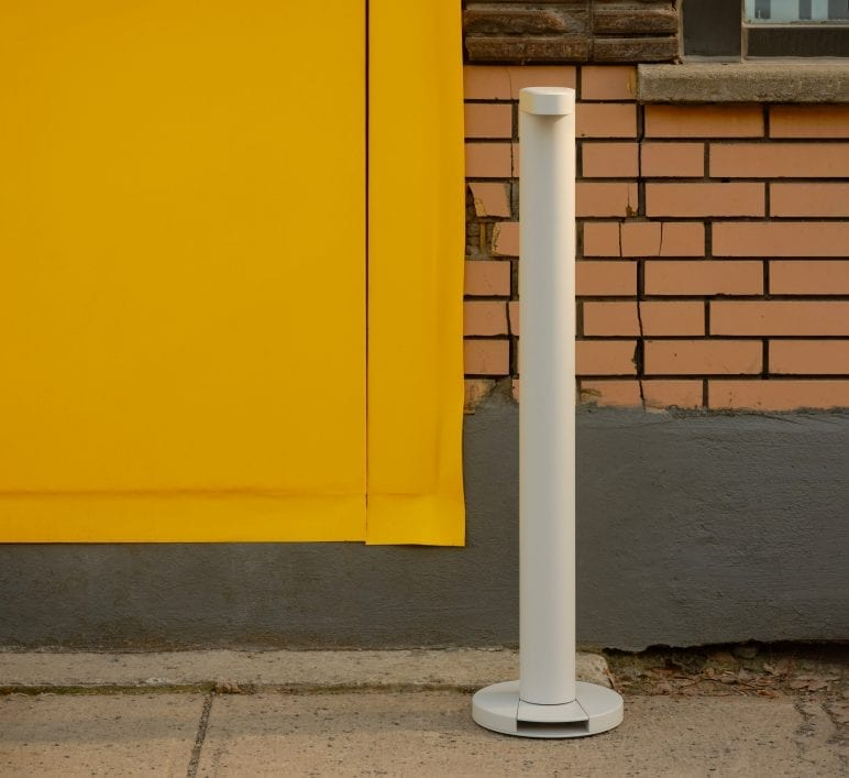 Image qui souligne l'esthétisme d'un Flaco blanc. Il est à l'extérieur d'un commerce avec une porte jaune.