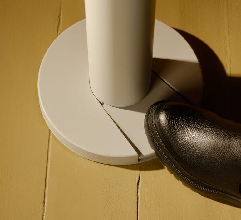 Image gros plan de la base d'un Flaco blanc. Un soulier noir appuie sur le mécanisme à pédale pour se laver les mains.